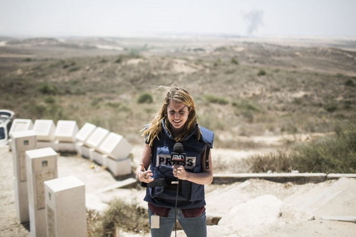 A TV reporter does a stand-up near the Israeli/Gaza border (Photo by Ilia Yefimovich/Getty Images)