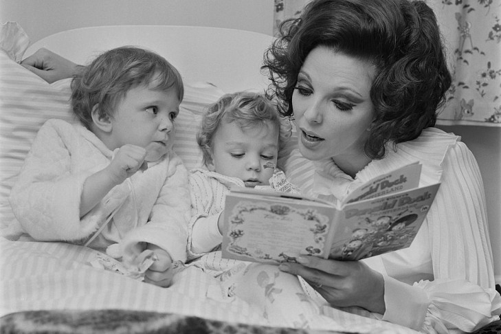 English actress Joan Collins, the wife of actor and singer Anthony Newley, reading a Donald Duck book to their two children Tara and Sacha, UK, 18th November 1967.  (Photo by Dove/Daily Express/Getty Images)