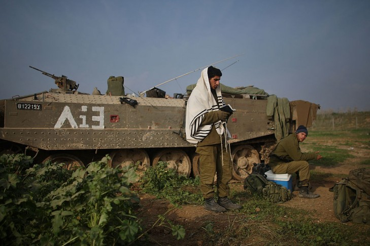 An Israeli soldier, just back from Gaza, prays beside his armored personnel carrier (APC) on January 17, 2009 along the Gaza-Israeli border in Israel.  (Photo by Spencer Platt/Getty Images)