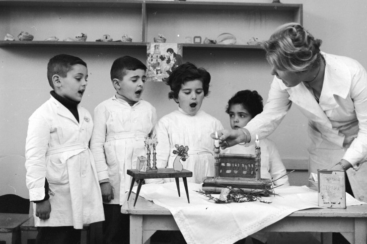 Schoolchildren observe the lighting of the candles on the Jewish Sabbath  (Photo by Evans/Three Lions/Getty Images)