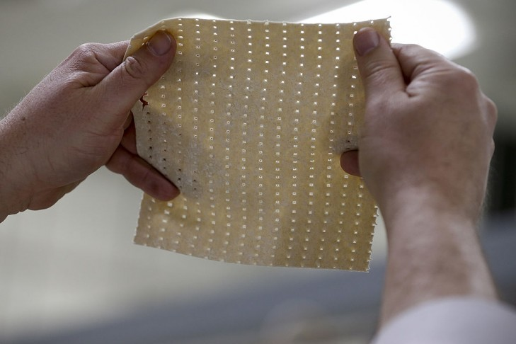 Rabbi Yaakov Horowitz examines the holes in a sheet of unbaked matzo from the matzo production line at the Manischewitz manufacturing facility on in Newark, New Jersey. Under strict rabbinical supervision at all times and in all stages of production, over 1 million sheets of matzo are produced daily during the height of the Passover season. (Photo by Jeff Zelevansky/Getty Images)