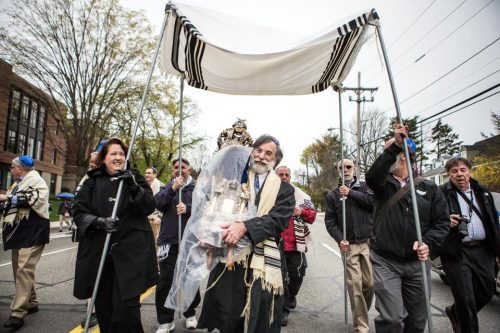 David Ehrmann carried a Torah scroll during a one-mile parade to dedicate Congregation Beth Shalom of the Blue Hills' new synagogue in Milton. (Aram Boghosian for The Boston Globe)