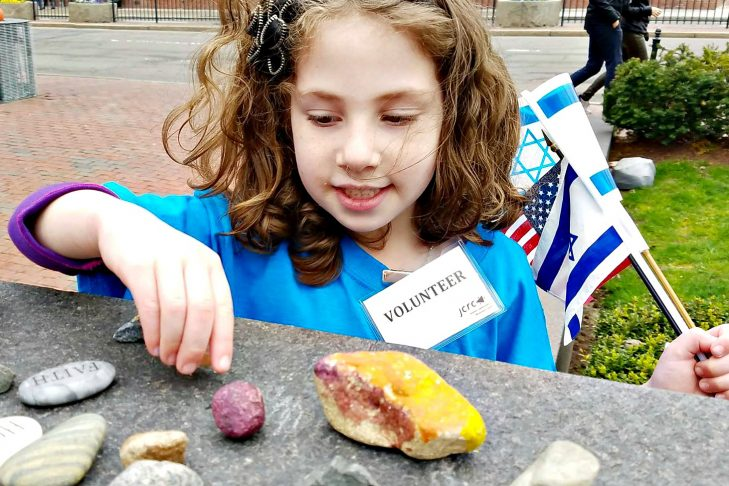 Sophie Einstein (5) places a rock at the New England Holocaust Memorial during the community Holocaust commemoration of Yom HaShoah (Photo courtesy of Boston 3G)