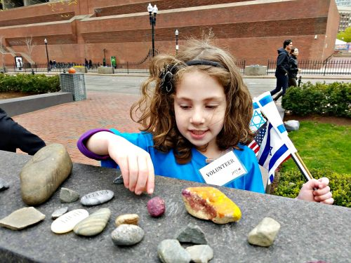 Sophie Einstein, 5, places a rock at the New England Holocaust Memorial during the community Holocaust commemoration of Yom HaShoah on Sunday. (Photo courtesy of Boston 3G)