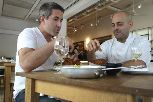 Michael Solomonov (left) and Meir Adoni at Mizlala in Tel Aviv tasting kubaneh, a Yemenite Sabbath bread.