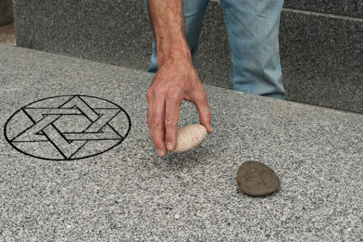 Placing stone on grave