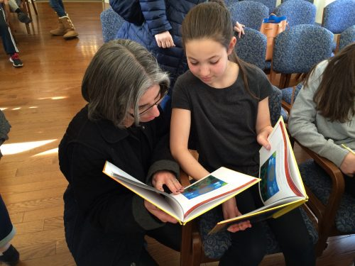 student showing her paintings in the final siddur to her mother
