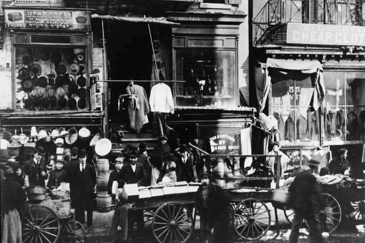 Shoppers in the mostly Jewish immigrant poplulation congregate as vendors sell their wares on the sidewalk outside of haberdasheries at 57 Hester Street and 55 Hester Street on the Lower East Side of Manhattan, New York circa 1900 (Photo by Hulton Archive/Getty Images)