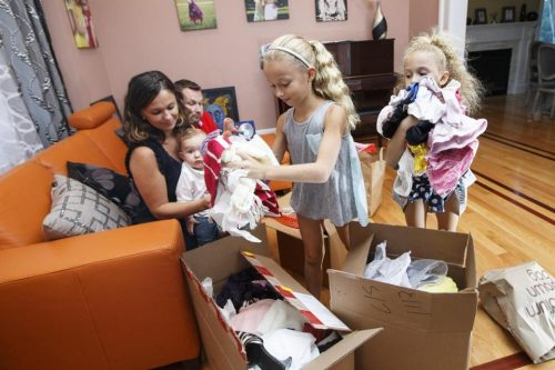 To mark the High Holidays, Viktoriya and Vlad Vilkomir of Newton, both emigrants from the former Soviet Union, and 10-month-old son Gabriel watch Giselle, 9, and Sophia, 7, pack gifts to be sent to an orphanage in Ukraine. (KEITH BEDFORD/GLOBE STAFF)