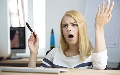 Angry young woman working on computer in office