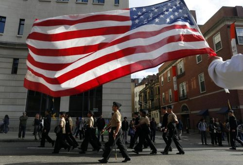 A man holds an American flag during a Veterans Day Parade in Boston. (JESSICA RINALDI/THE BOSTON GLOBE)