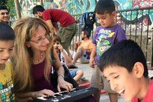 Judy Stillman, a professor of music at Rhode Island College, played a miniature keyboard for children at a refugee camp outside of Athens. (JUDY STILLMAN)