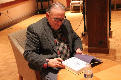 """Archie Rand signs copies of his book """"The 613"""" at Temple Emanuel in Newton. (Courtesy Jewish Arts Collaborative)"""