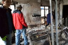Haifa area college students inspect the damage to an apartment with the owner in the Romema neighborhood of Haifa.